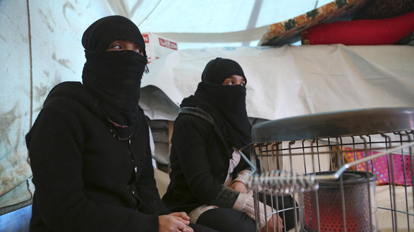 Internally displaced Yazidi women warm themselves by a heater inside their tent at a refugee camp in Bamarny village in Dahuk of the Kurdistan region.