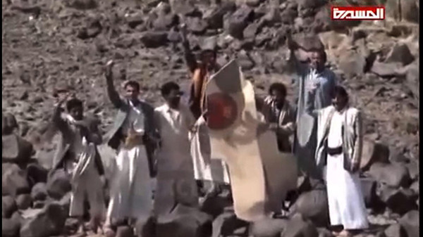Yemeni tribesmen celebrating around the wreckage of a plane bearing a Moroccan flag, in the the Wadi Nushur area in the north Yemen's province of Saada, on May 11, 2015.