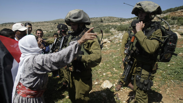A Palestinian woman debates with Israeli soldiers during a protest against the expansion of the Elon Moreh Israeli settlement in the village of Salem near Nablus on the West Bank.