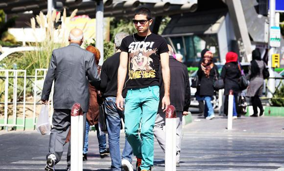 An Iranian trendy youth listens to music as he walks through central Tehran, in this October 17, 2013 file photo.