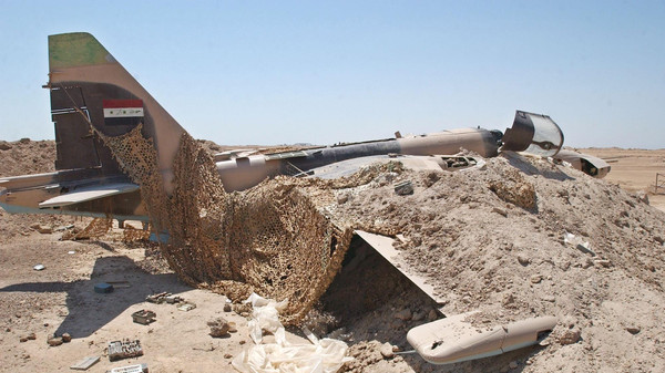 An Iraqi Air Force SU 25 fighter jet wrapped in plastic sits buried in the sands of the deserted Tamous air base.