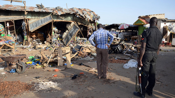 A police officer stands at the scene of a bombing after at least 20 people were killed when a young female suicide bomber detonated her explosives at a bus station in Maiduguri, northeast Nigeria, on June 22, 2015.