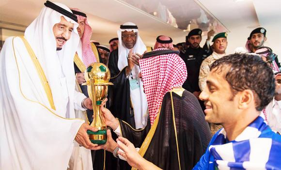 Custodian of the Two Holy Mosques King Salman hands the King's Cup trophy to Al-Hilal captain Mohammed Al-Shalhoub at the King Abdullah Stadium in Jeddah on Friday. (SPA)