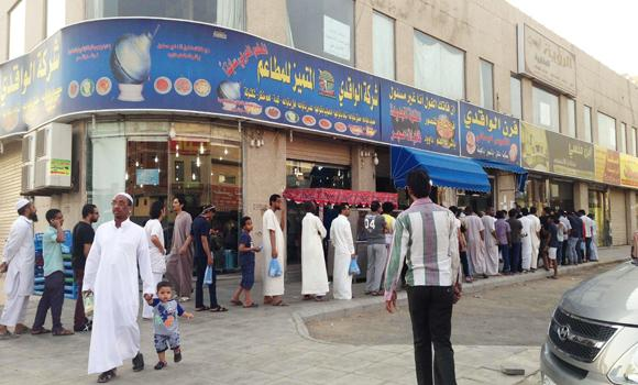 Customers stand in line to buy ful outside a shop in Makkah.