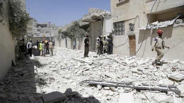 Civilians and civil defense members inspect a site hit by what activists said was a sea mine dropped by forces loyal to Syria's President Bashar al-Assad in Maaret al-Naaman town in Idlib province June 4, 2015.