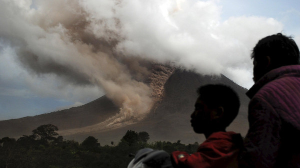 Residents sit on their motorcycle as they watch an eruption at Mount Sinabung, in Namanteran village in Karo Regency, Indonesia's North Sumatra province, June 14, 2015.