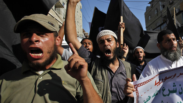 In this Thursday, Aug. 22, 2013 file photo, Palestinian members from Youth Salafists group chant slogans while waving their black flags in Rafah Refugee Camp, southern Gaza Strip.