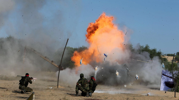 Palestinians from the Democratic Front for the Liberation of Palestine (DFLP) demonstrate their skills at a scene simulating an attack on an Israeli site during a military graduation ceremony in Rafah in the southern Gaza Strip.