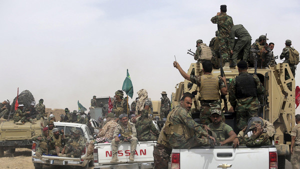 Shiite paramilitaries riding military vehicles travel from Lake Tharthar toward Ramadi to fight against ISIS militants.