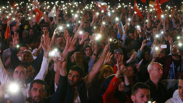 Supporters hold up their mobile phones outside the AK Party headquarters in Ankara, Turkey, June 7, 2015.