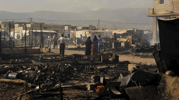 People inspect the tents that were burnt in a refugee camp for Syrian refugees in Lebanon's Bekaa Valley June 1, 2015.