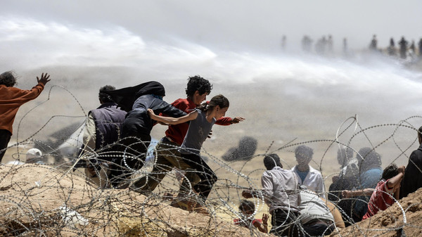 Syrian refugees run away as Turkish soldiers use water cannon to move them away from fences at the Turkish border near the Syrian town of Tal Abyad, at Akcakale in Sanliurfa province, on June 13, 2015.