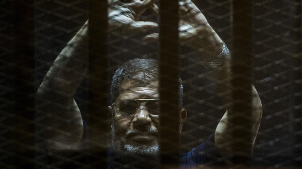 A file picture taken on June 2, 2015 shows ousted Egyptian president Mohamed Morsi gesturing from the defendants cage as he attends his trial at the police academy on the outskirts of the capital Cairo.