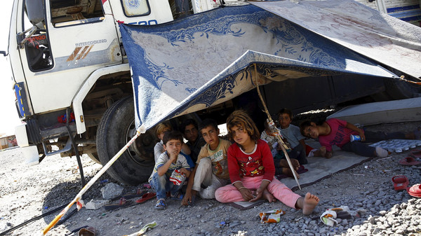 Syrian refugee children from the northern Syrian town of Tel Abyad sit under a make shift tent pitched up next to a truck in Akcakale, in Sanliurfa province, Turkey, June 18, 2015.