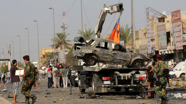 Security forces watch a tow truck lift a destroyed vehicle at the site of a car bomb explosion in the largely Shiite eastern neighborhood in Baghdad, Iraq.