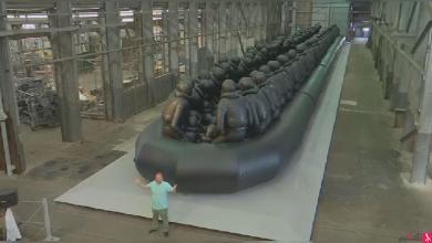 Photo of مجسم ضخم لقارب مطاطي يروي معاناة المهاجرين