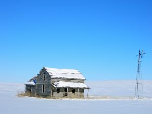 Old homestead and windmill stand alone in the snow covered pasture.