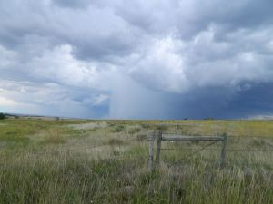 Storm cell on the prairie, with fence in foreground
