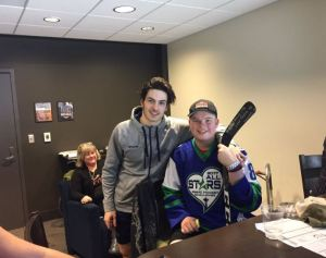 Hockey Player Mathew Barzal and Bretton pose with a signed stick