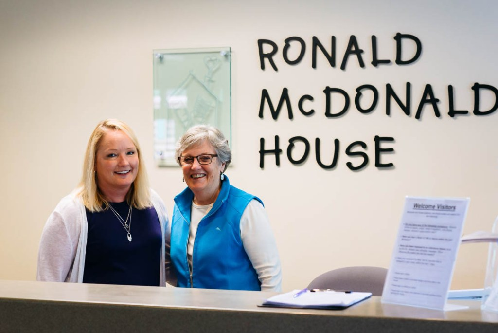 Ruth Fox stands with another volunteer at the Seattle House front desk