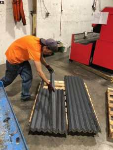 SMF employee setting down a corner brace on a pile of other corner braces