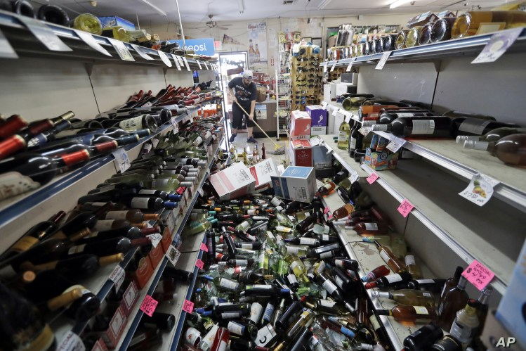 Bottles of wine are strewn in the middle of an aisle as Victor Abdullatif, background center, mops inside of the Eastridge Market, his family's store, July 6, 2019, in Ridgecrest, Calif.