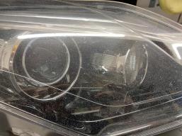 Světlomet po 200 000km ostřílený tisícem kamínků. Na foto stav umytého reflektoru, přesto vypadá díky poškozenému plexi jako špinavý.