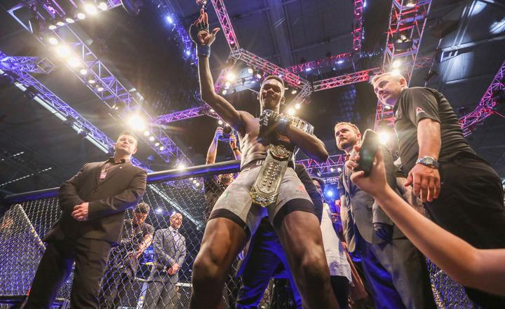 Israel Adesanya celebrates winning the UFC middleweight world title belt.