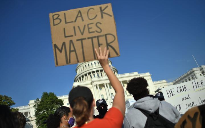 Protesters hold signs as they demonstrate in front of the United States Capitol in Washington, DC, on 2 June, 2020.