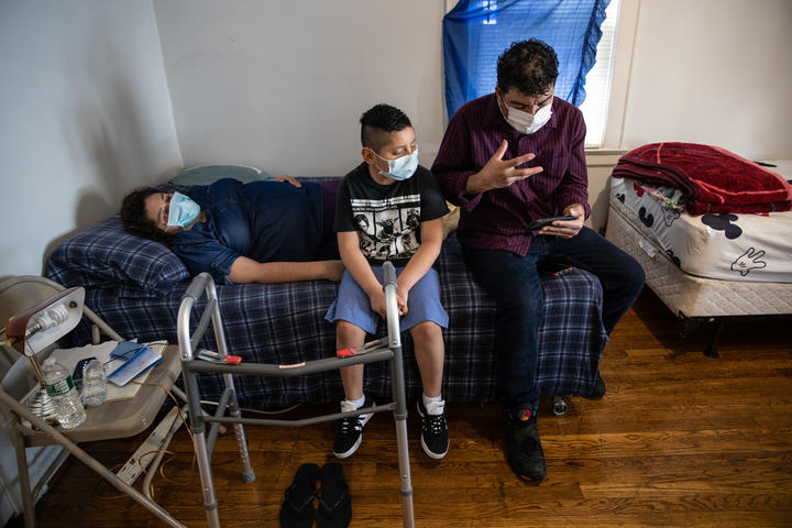 Connecticut residents Zully (left), Marvin (right), and Junior, 7, talk to a doctor via Zoom while recovering from COVID-19 at home.
