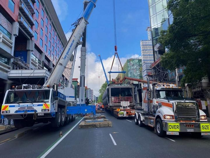 Mobile cranes putting the SkyCity pedestrian bridge in place over Hobson Street.