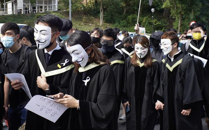 Students from the Chinese University of Hong Kong (CUHK), wearing graduation gowns and and masks, take part in a protest march in memory of the pro-democracy demonstrations at CUHK a year ago,  in the Shatin area of Hong Kong on November 19, 2020.