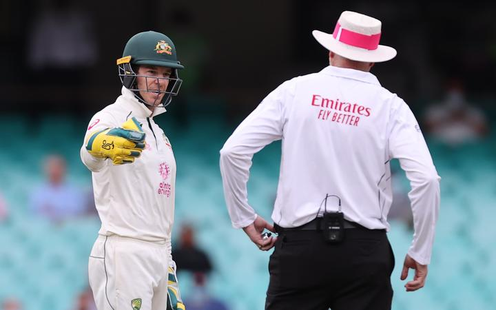 Australia's captain Tim Paine (L) speaks with an umpire during the second day of the third cricket Test match between Australia and India at the Sydney Cricket Ground (SCG) in Sydney on January 8, 2021.