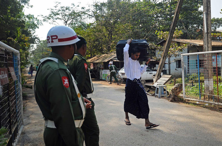 A former Myanmar child soldier (R) carries his belongings as he walks out from a military compound in Yangon after a ceremony discharging a group of children and young people back to their parents and guardians on January 18, 2014.