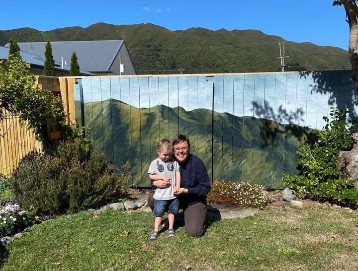 Artist Hana Carpenter and her son in front of the mural of the hills.