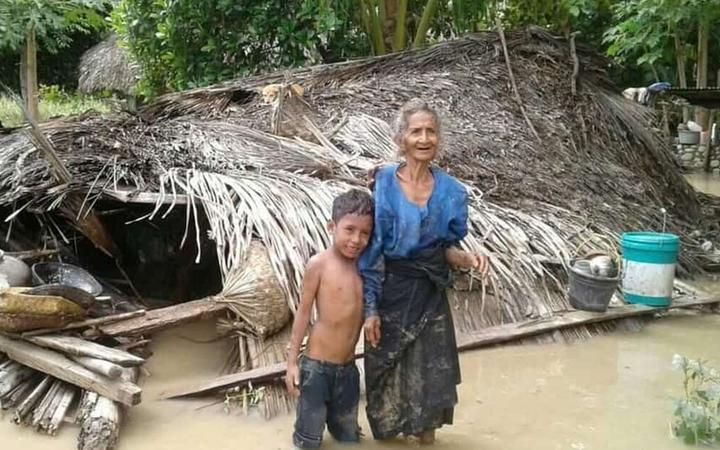 An elderly villager and her grandson stand in floodwaters in front of their damaged home in the village of Haitimuk in East Flores on April 4, 2021, after flash floods and landslides swept eastern Indonesia and neighbouring East Timor.