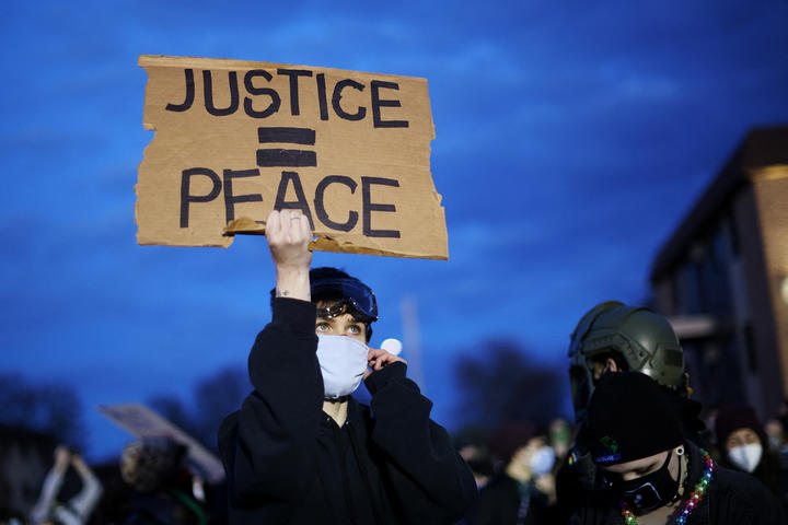 A demonstrator holds up a sign during a protest outside the Brooklyn Center police station on 17 April, in Brooklyn Center, Minnesota.