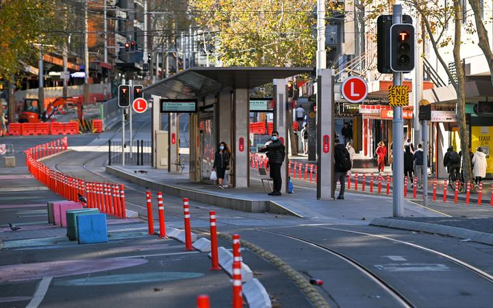 People wait for a tram in the empty central business district in Sydney on June 27, 2021, on the first full day of a two-week Covid-19 coronavirus lockdown to contain an outbreak of the highly contagious Delta variant.