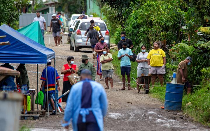 Residents look on as police check people are wearing face masks in Suva,  as a worsening outbreak of the Covid-19 coronavirus Delta variant has overwhelmed the South Pacific nation's largest hospital.