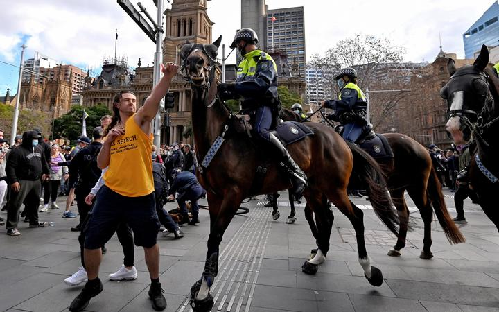 A protester (left) tries to push away a police horse in Sydney, as thousands of people gathered to demonstrate against the city's month-long stay-at-home orders.
