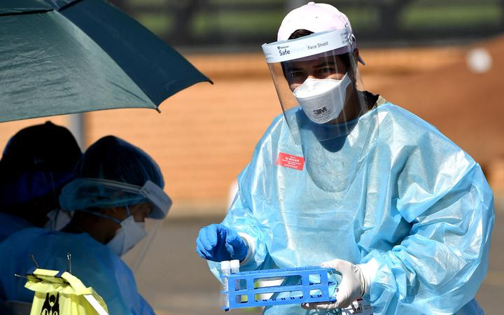 A health worker collects swab samples at a Covid-19 coronavirus drive through testing site in the Smithfield suburb of Sydney on August 12, 2021.
