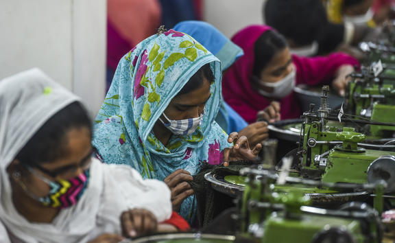 Labourers wearing facemasks work in a garment factory during a government-imposed lockdown as a preventative measure against the COVID-19 coronavirus in Asulia, on the outskirts of Dhaka on April 7, 2020.