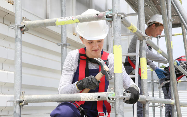 Young woman in professional training working on scaffolding, construction.