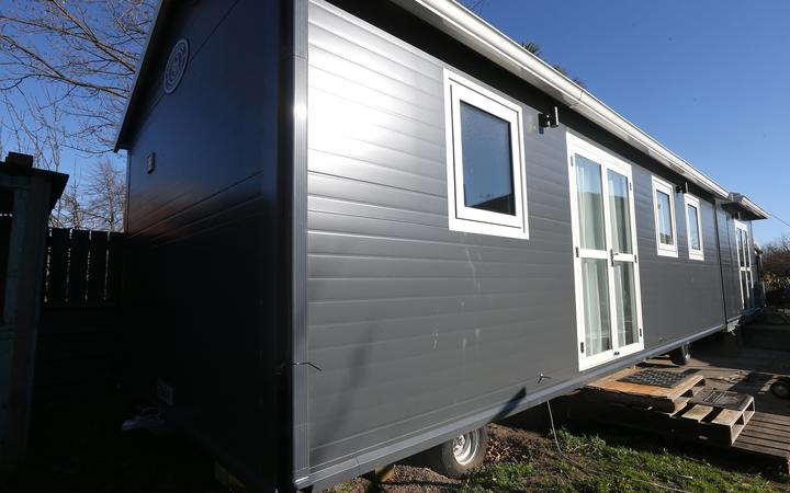 A tiny house on wheels in the backyard of a Renwick house,
