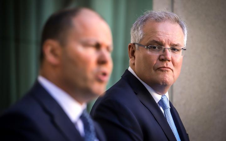 Australian Prime Minister Scott Morrison (R) reacts as he stands with the Australian Treasurer Josh Frydenberg
