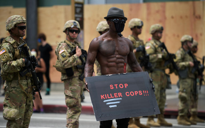 A protester holds a placard in front of a row of Army National Guard during a demonstration over the death of George Floyd in Hollywood