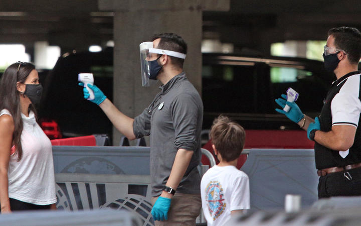 Visitors have their temperatures checked as they arrive at Universal Studios theme park on the first day of reopening after the shutdown during the coronavirus pandemic, on June 5, 2020, in Orlando, Florida.