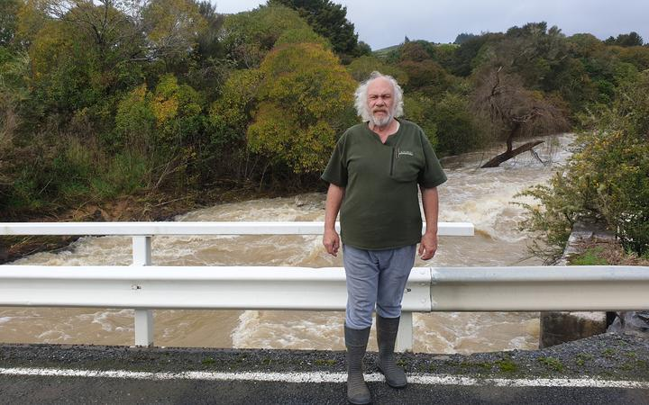 Mike Butler on a bridge above the raging Waiharakeke Stream