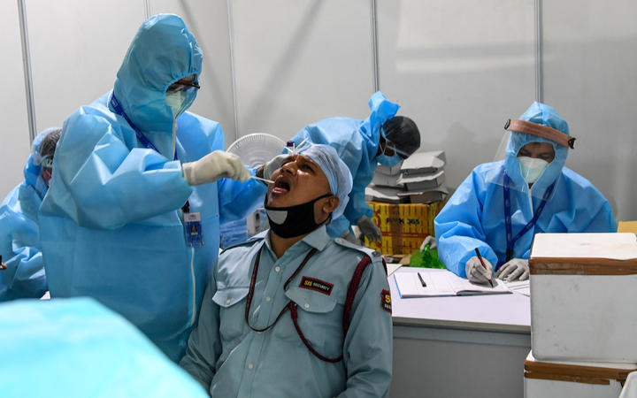 Medical staff taking a swab sample from a man at Dr Ram Manohar Lohia (RML) hospital in New Delhi on 31 July.