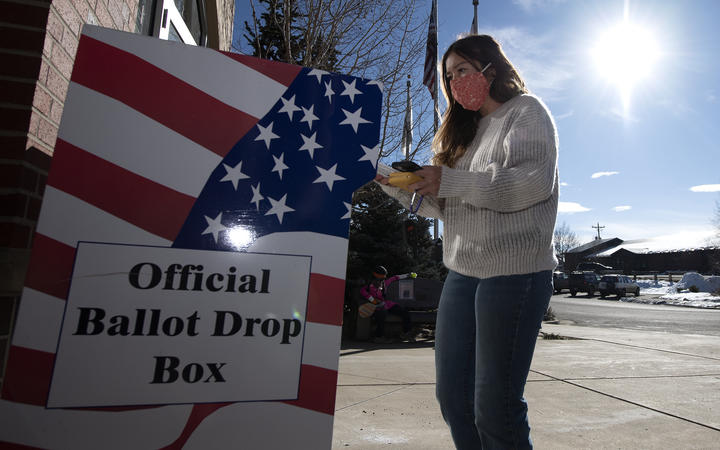 A voter drops of her ballot at the Granby Town Hall  in Granby, Colorado on November 3, 2020.